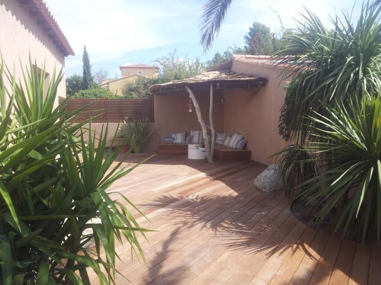 Terrasse exotique avec spa, coin détente et bois flotté